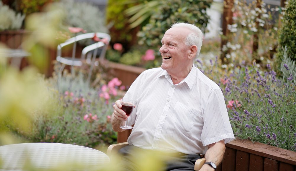 Resident having a drink in the garden at Albert Edward Prince of Wales Court
