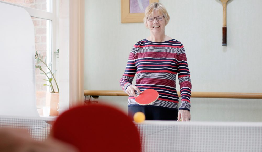 Resident playing table tennis at Devonshire Court