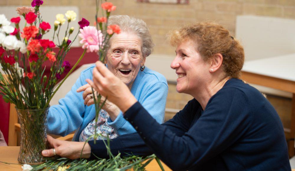 Resident and staff member flower arranging at Prince Edward Duke of Kent Court