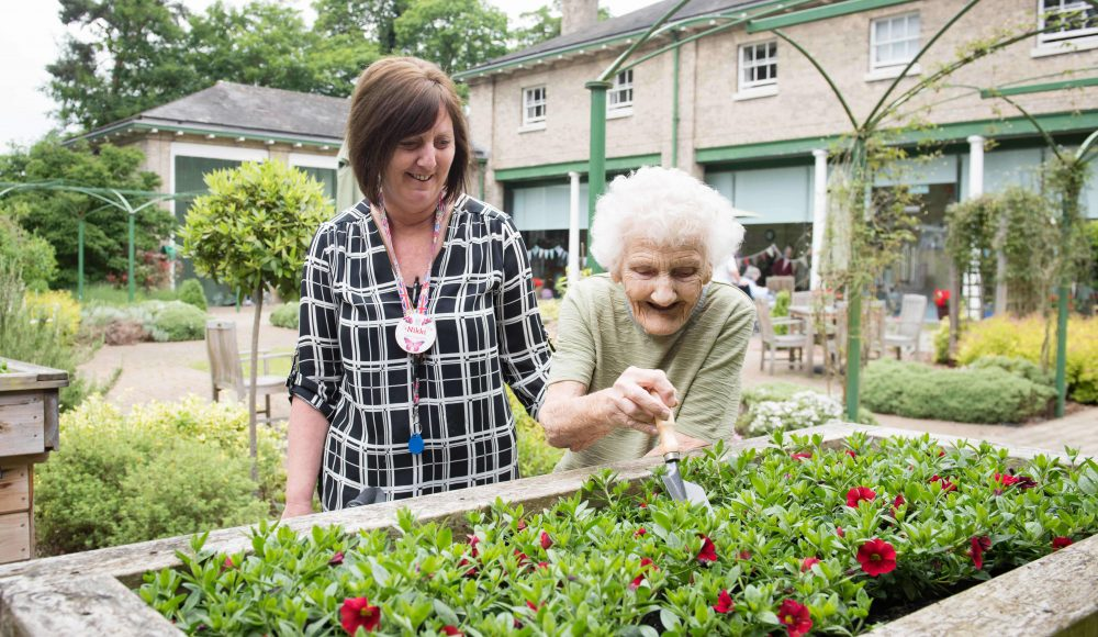 Resident and staff member in gardens at at Prince Edward Duke of Kent Court