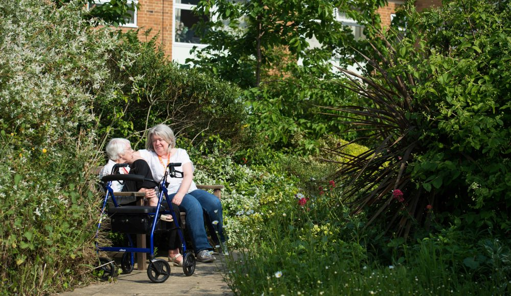 Resident and staff member in the garden at Lord Harris Court