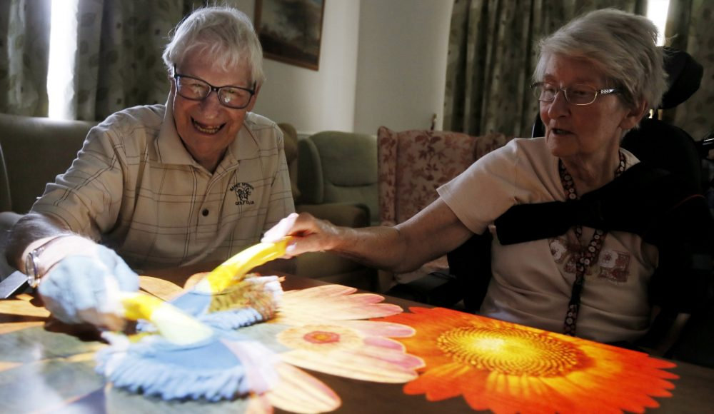 Residents and relatives using magic table technology at Lord Harris Court