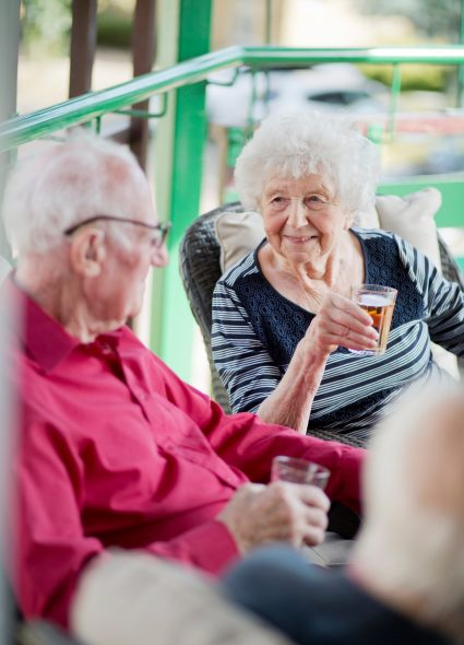 Residents having a drink in the gardens at Prince Michael of Kent Court