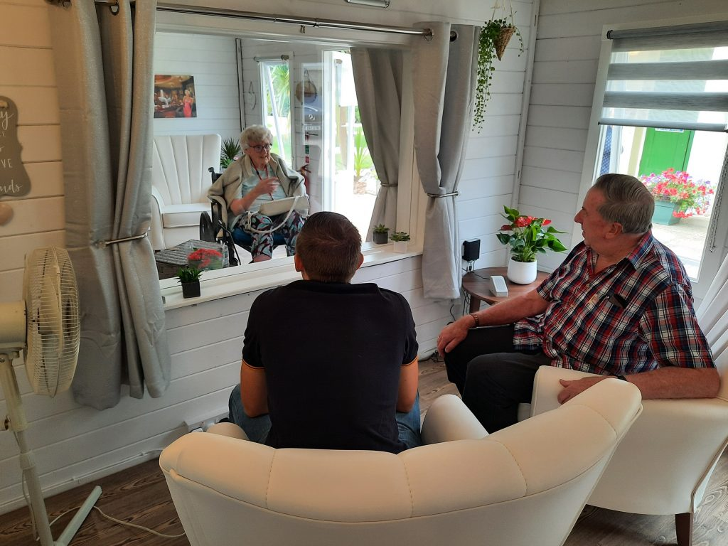 Resident and family members in visitor pod at Prince Edward Duke of Kent Court