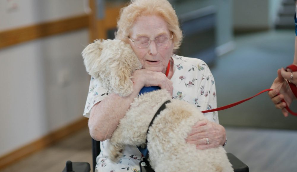 Resident durning an activities session gets to pat a young dog