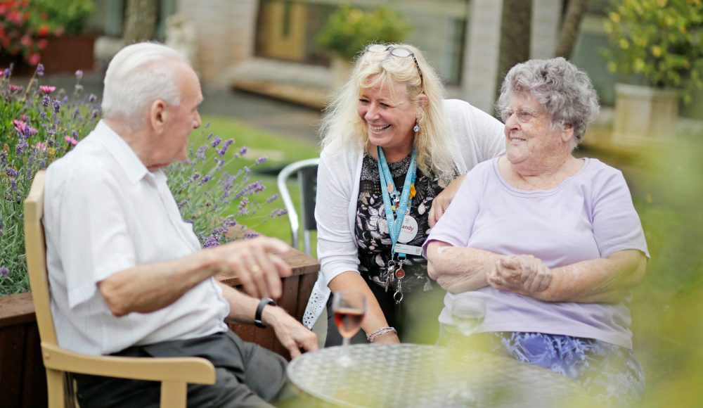 Staff member and residents in the garden at Albert Edward Prince of Wales Court