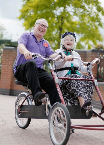 Resident and staff on tandem bicycle at Devonshire Court