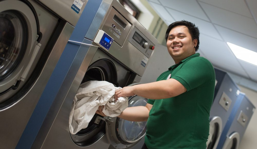 Staff member doing laundry at Cadogan Court