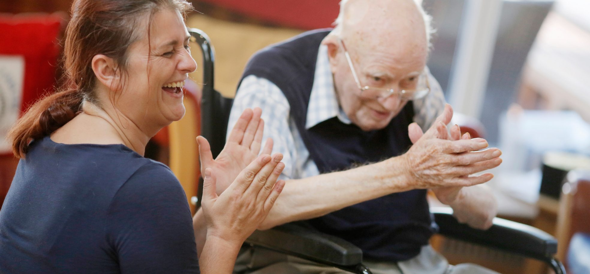 Resident and staff member clapping hands at The Tithebarn