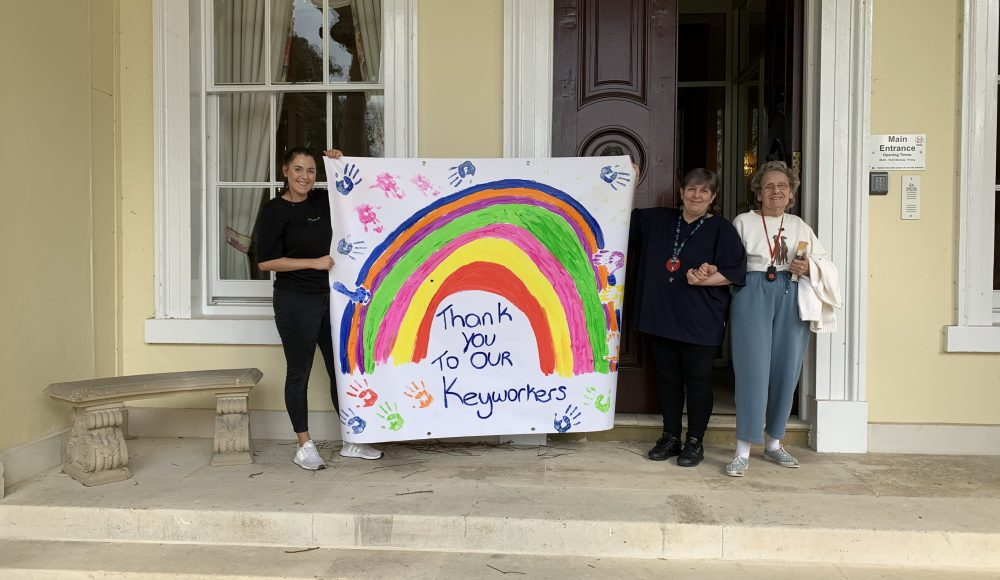 Residents hold up rainbow art to thank key workers at Prince Edward Duke of Kent Court