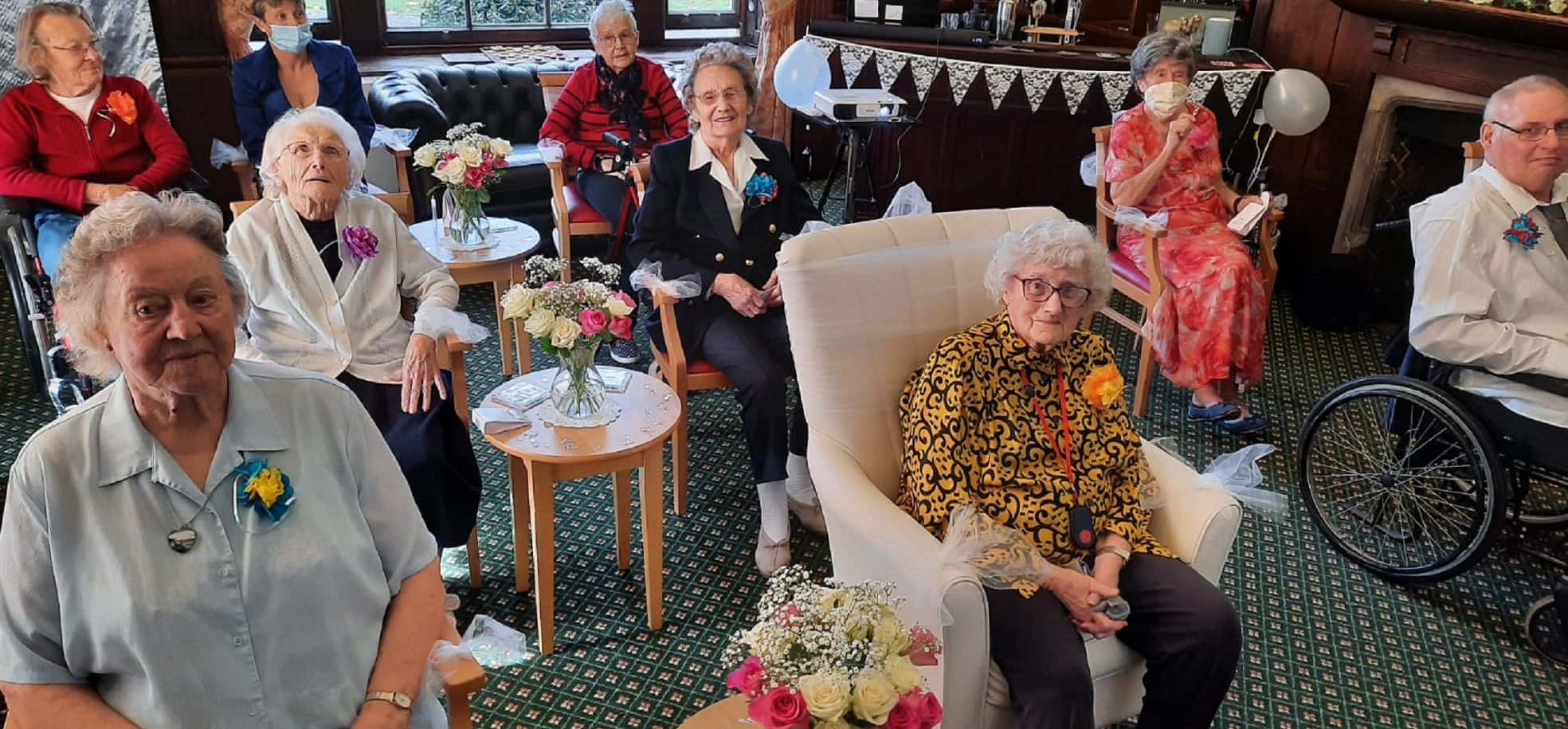Prince Edward Duke of Kent Court resident Dot Bash (wearing a yellow patterned blouse) watching a live stream of her granddaughter's wedding with fellow residents.