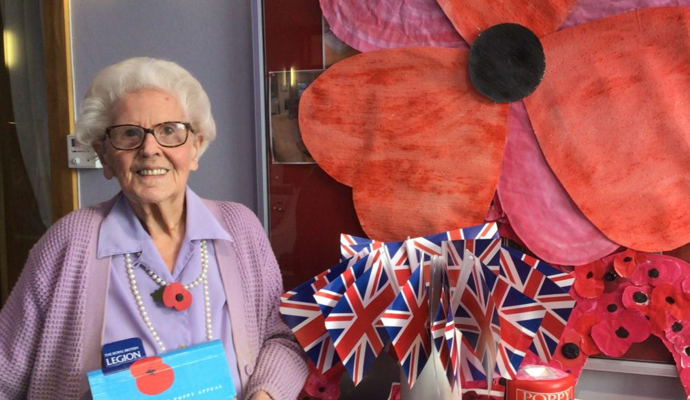 Connaught Court resident, Joan Brown, aged 99, in front of the Home's Remembrance Day display with her poppies.