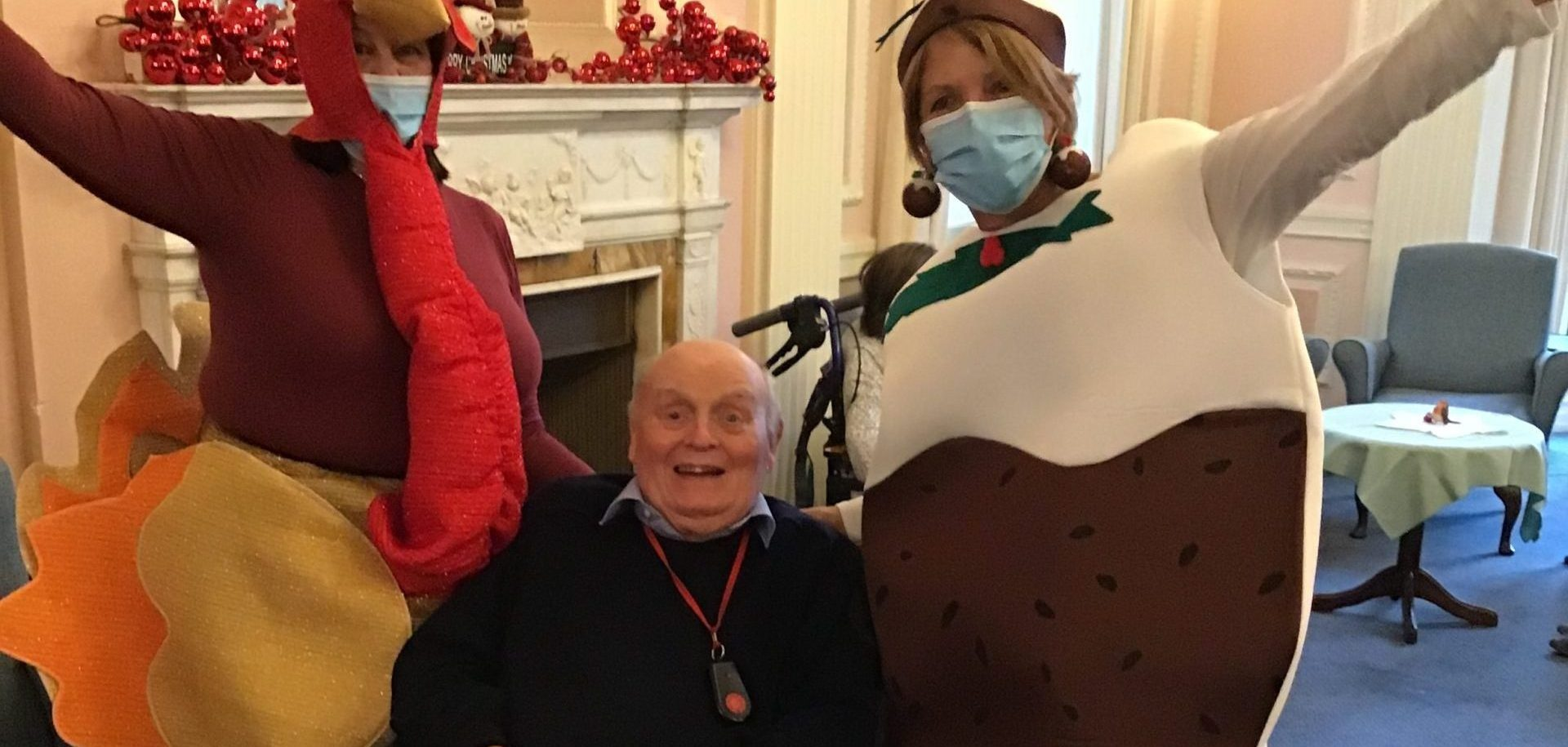 Staff in Christmas dress up with resident at Zetland Court