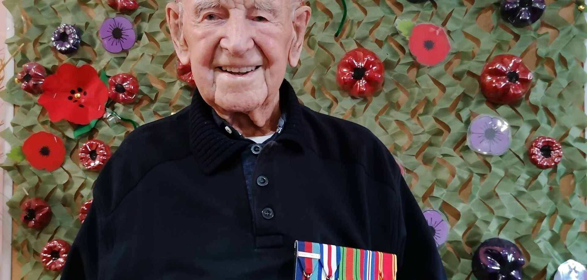 Scarbrough Court resident and WWII veteran Joe Dixon, aged 107, in front of the Home's Remembrance Day display
