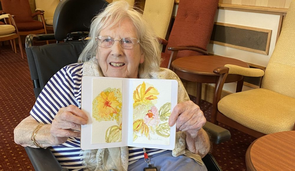 Resident Christine Goody, aged 85 at RMBI Care Co.Home Queen Elizabeth Court with her flowers painting