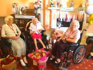 Residents Joycelyn Mills (left) and Kathleen Powis (right), who are 101 and 100 years old, respectively, congratulates Nina Ansell on her 100th birthday. Together, the three ladies have a combined age of 301.
