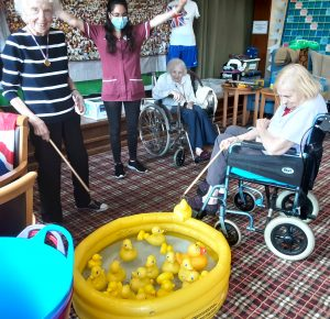 Residents Coral McGuillvray and Angela King engage in a hook a duck game while resident Irene Muggeridge and staff member Neus Amoros cheer on them.