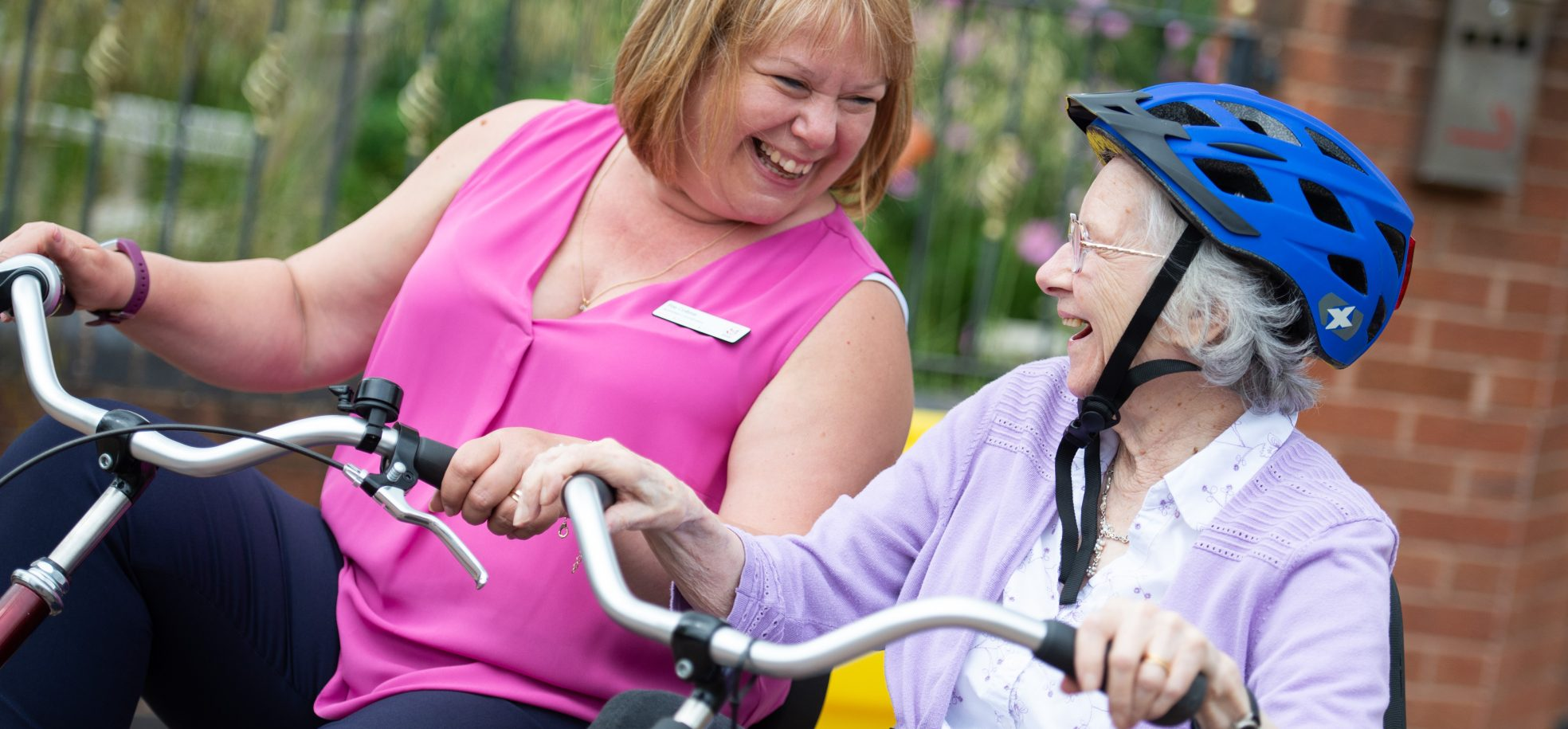 Staff member and resident riding a bike together at Devonshire Court, Leicester.